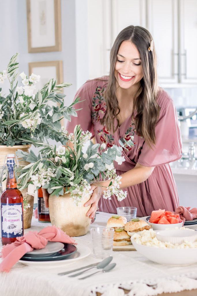 Brunette in mauve maxi dress placing greenery and floral centerpiece on sophisticated Labor Day tablescape