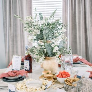 Sophisticated Labor Day tablescape set with woven tassel blanket, Labor Day food ideas and floral centerpieces in wood vases