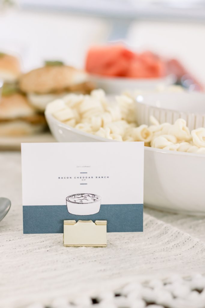Blue and white food label for chips and dip pairing party standing with a standard gold binder clip