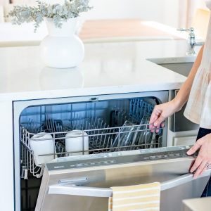 woman opening whirlpool dishwasher