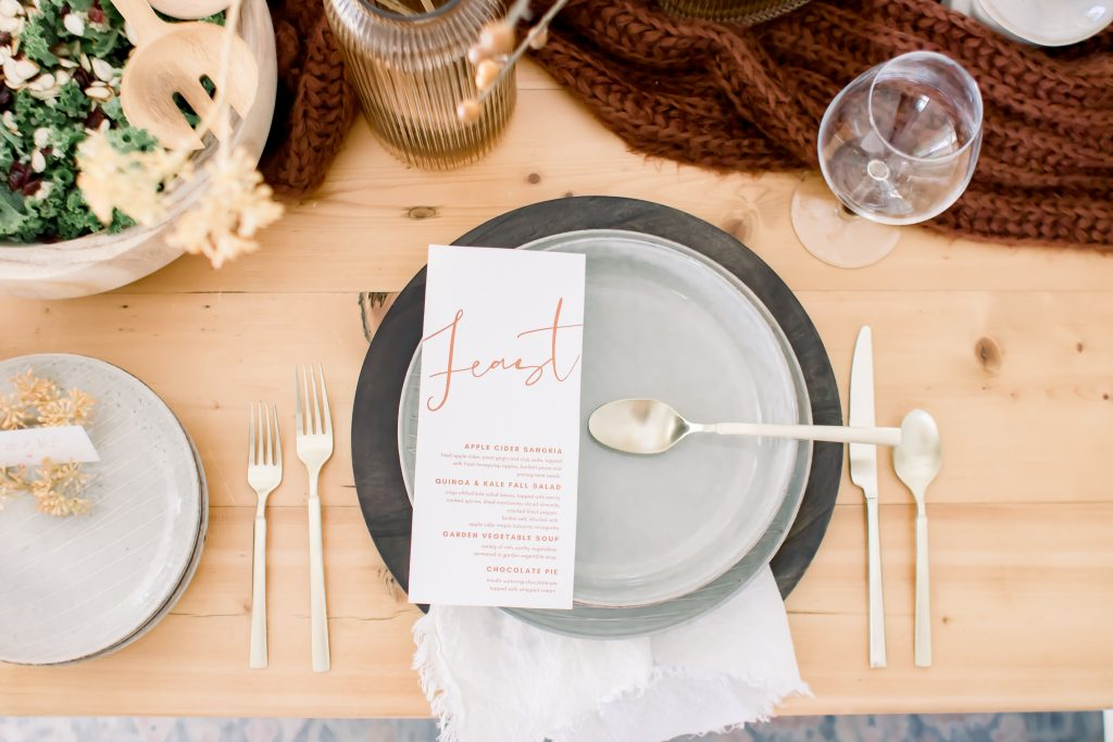 Light grey dinnerware set with dark wood charger and champagne flatware for an intimate Fall tablescape