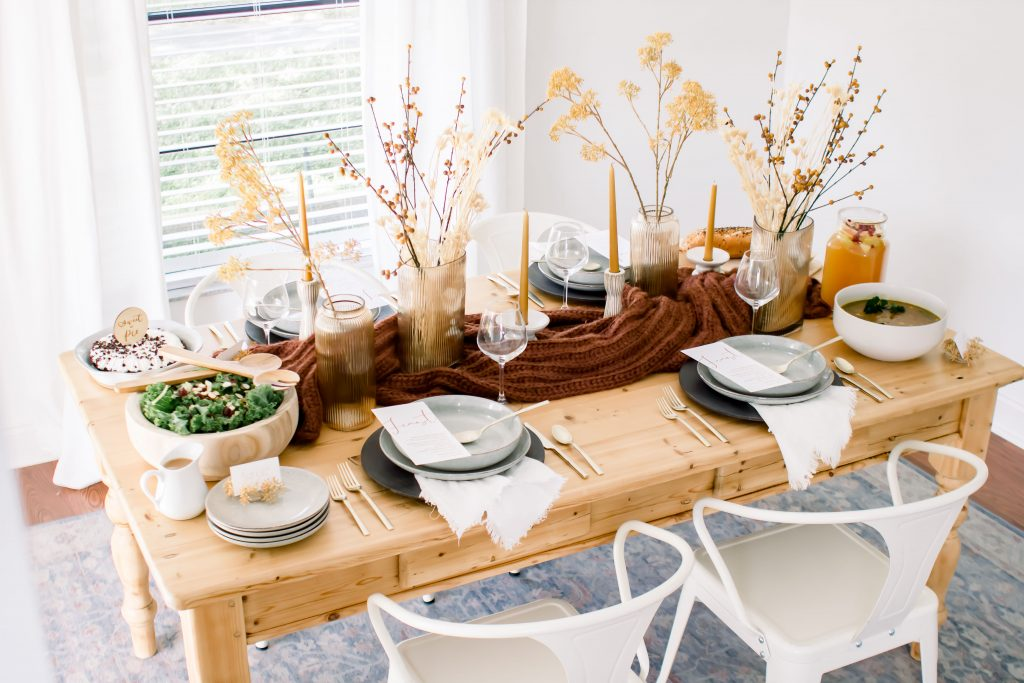 Light wood dining table with white metal chairs set with Fall decor for an intimate Fall tablescape
