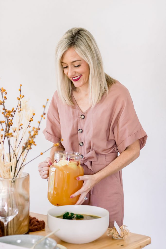 blonde woman holding a pitcher of apple cider sangria