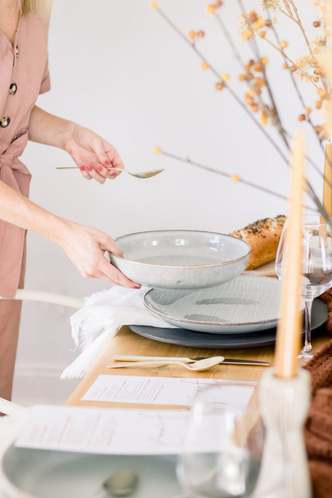 Hands setting light grey dinnerware atop intimate Fall tablescape