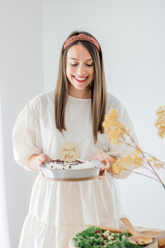 woman wearing white dress holding chocolate pie recipe