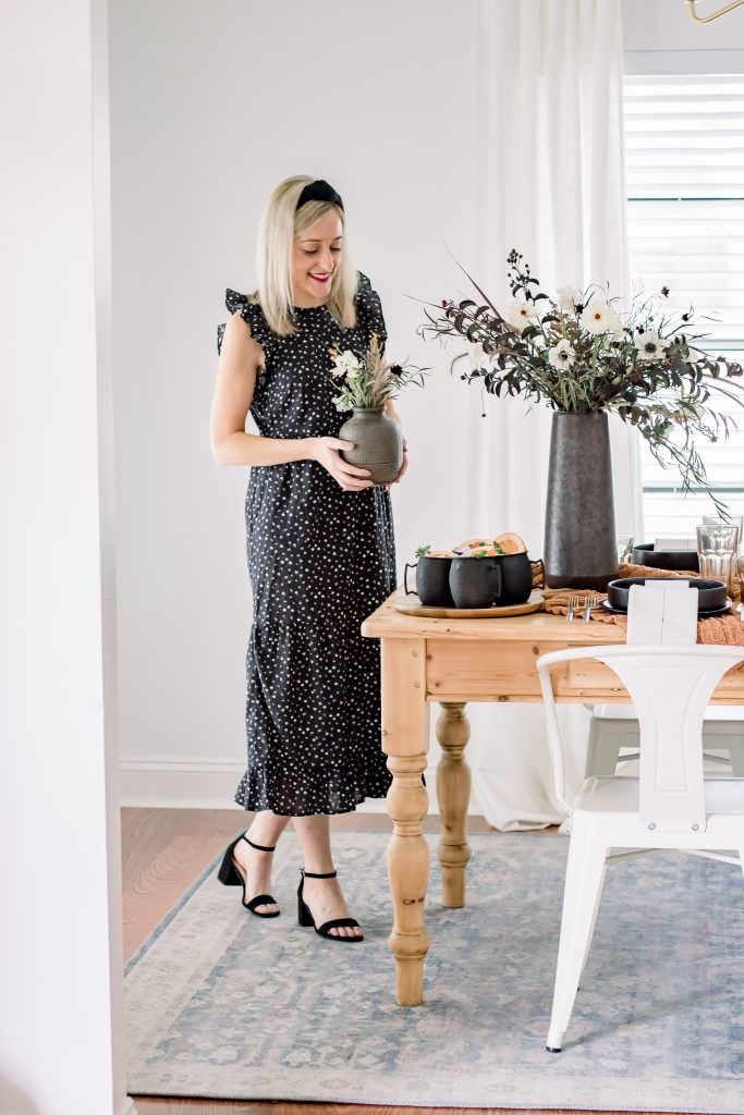 blonde woman wearing ruffle dress from target and setting a sophisticated halloween tablescape