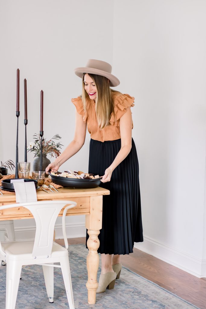 woman setting the table with a cast iron pan from Chrissy Teigan full of s'mores