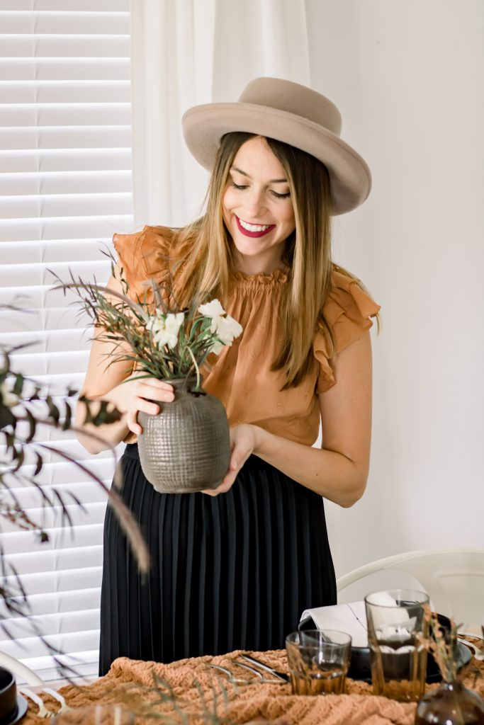 woman wearing golden ruffle shirt and black pleated skirt from target smiling and holding a clay vase from old time pottery filled with flowers