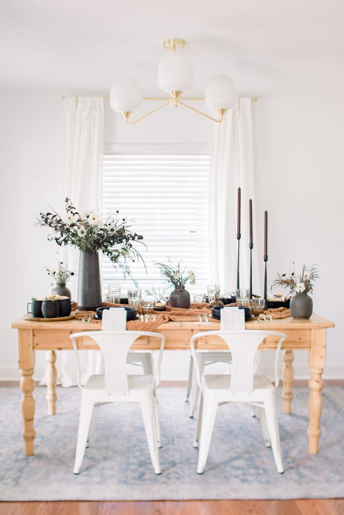 sophisticated halloween tablescape on a wooden farmhouse table with white metal dining chairs tall black taper candlesticks and fall floral centerpieces