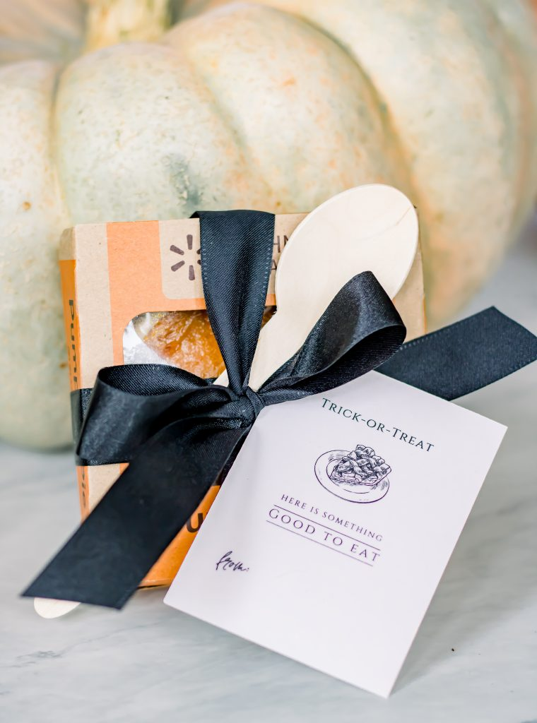 Mini pumpkin pie box tied with black bow, a wooden spoon and a Halloween gift tag