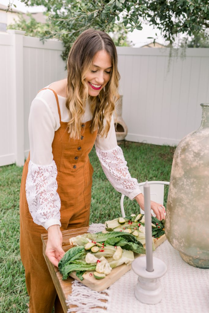 woman wearing romper from Old Navy setting a Friendsgiving tablescape
