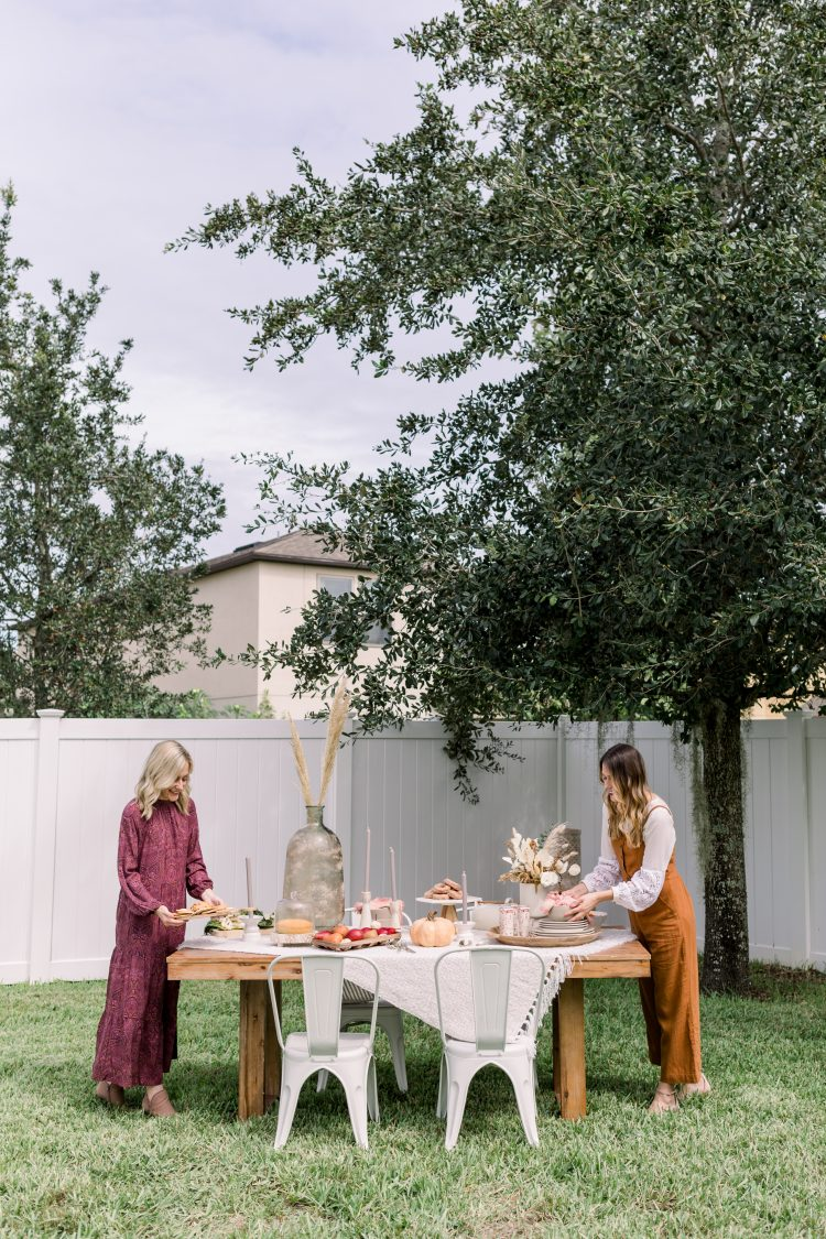 two women setting an outdoor dining table for Friendsgiving