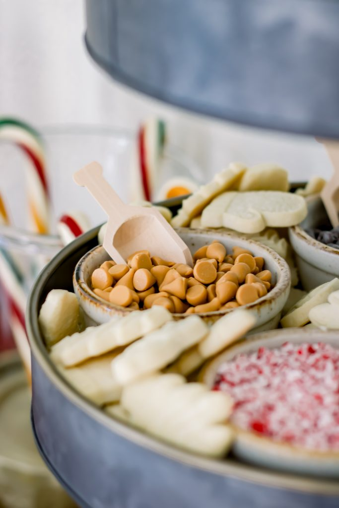 Bowl full of butterscotch morsels with a mini wooden spoon for gourmet hot chocolate bar