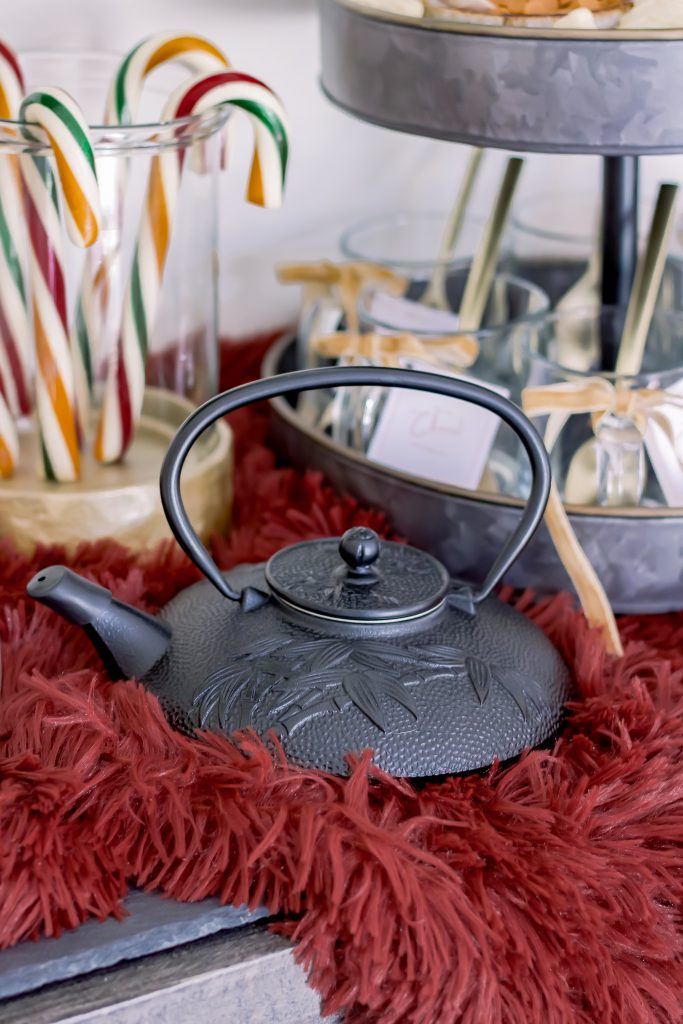 Black iron kettle set on red fur blanket for a gourmet hot chocolate bar