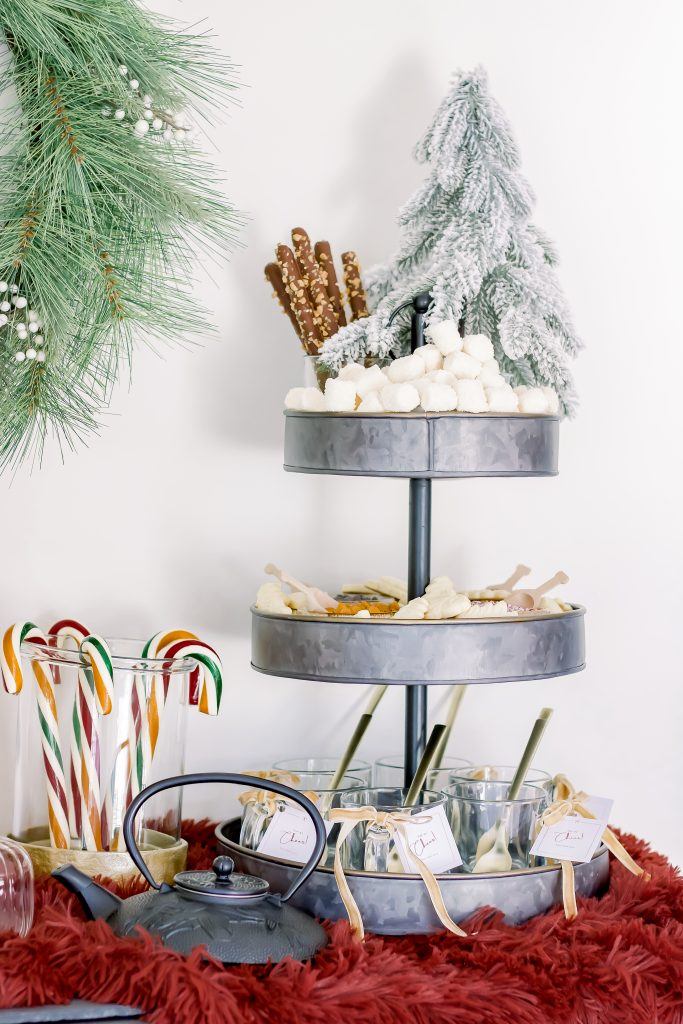 Three tier black galvanized dessert tray filled with gourmet hot chocolate bar toppings