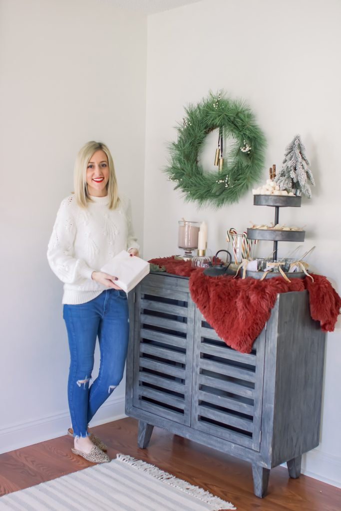 Blonde female in white sweater holding Cotier Brand's Convokins in front of a Gourmet Hot Chocolate Bar