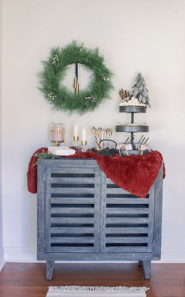 Gourmet Hot Chocolate Bar styled on a black slat cabinet with red fur blanket