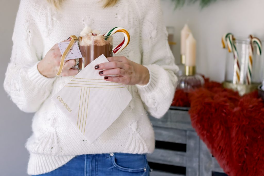 Female in white chunky sweater holding a clear mug of hot chocolate topped with marshmallows and candy cane
