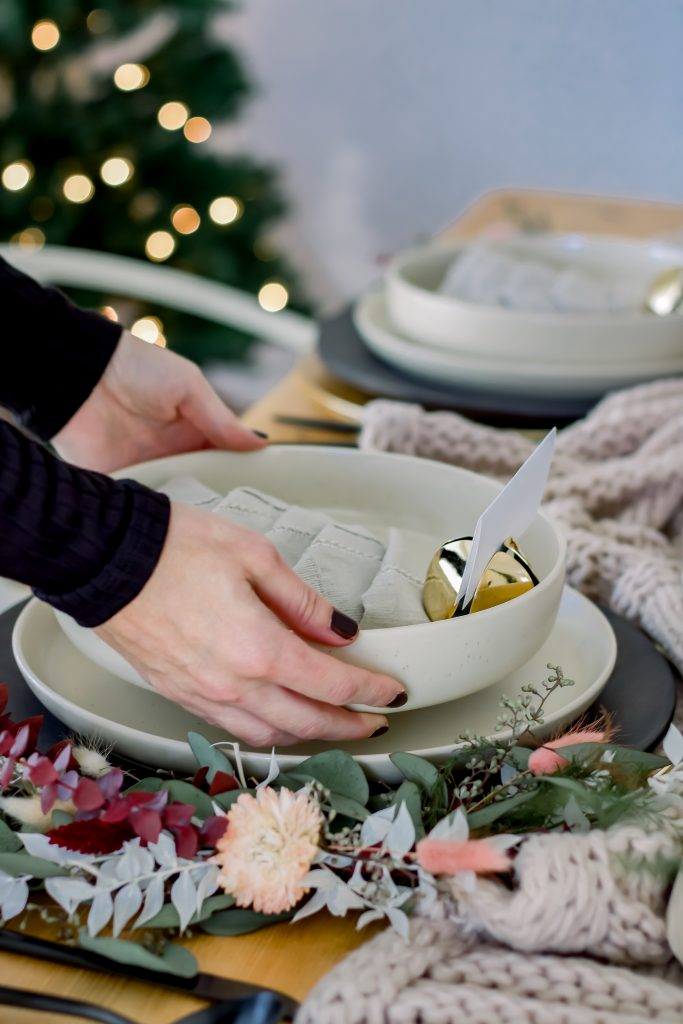 Two hands setting an ivory stoneware bowl on a sophisticated Christmas tablescape