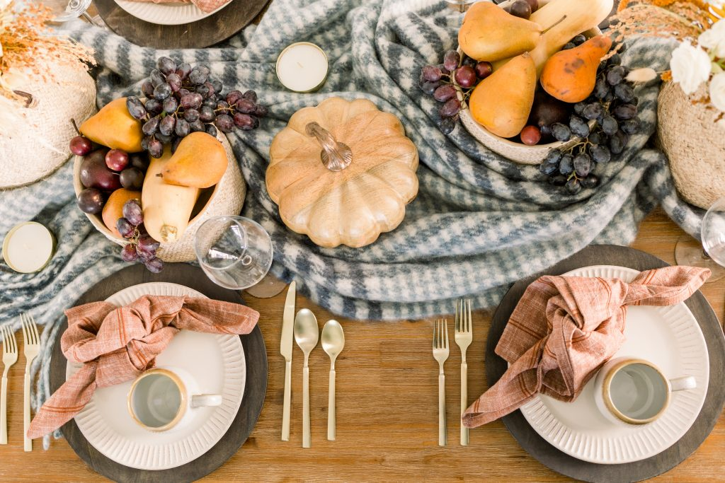 thanksgiving table set with blue and white plaid, gold flatware, and stoneware