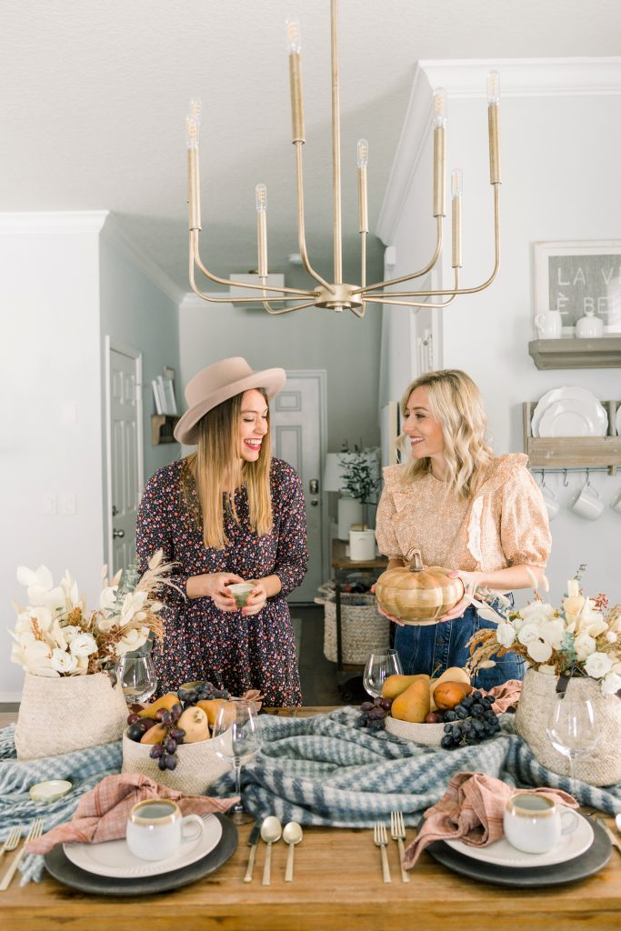 two women setting a Thanksgiving tablescape