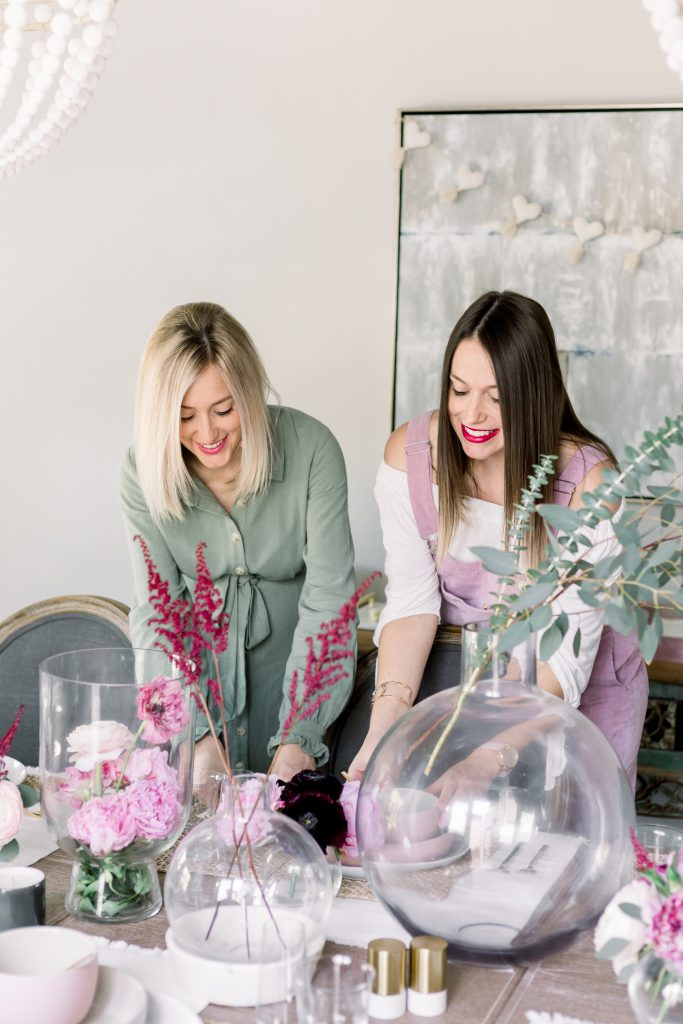 Two women setting a pink and burgundy Valentine's Day tablescape