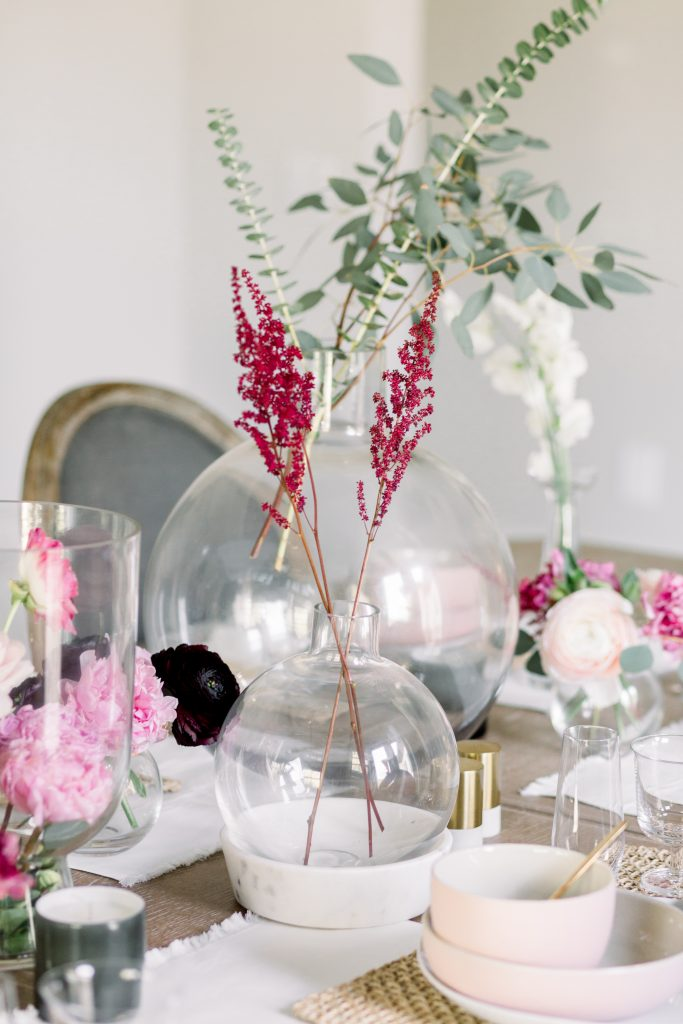 Clear vases filled with greenery, pink and burgundy floral for Valentine's Day