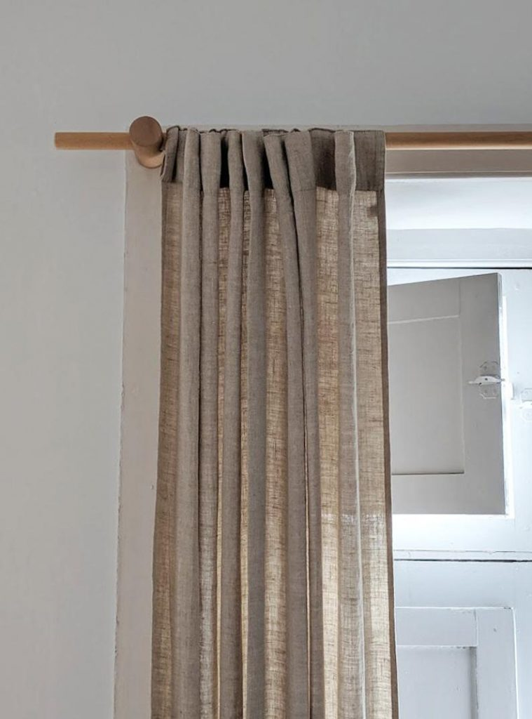 Round wood curtain rod holders and tan curtains