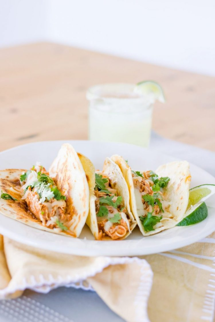 three tacos on white plate with beverage in background