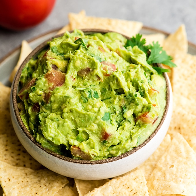 homemade guacamole in a beige bowl over a plate of tortilla chips