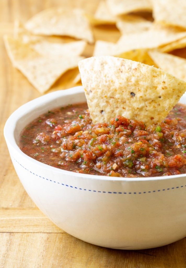 a tortilla chip being dipped into a bowl of salsa with more chips in background