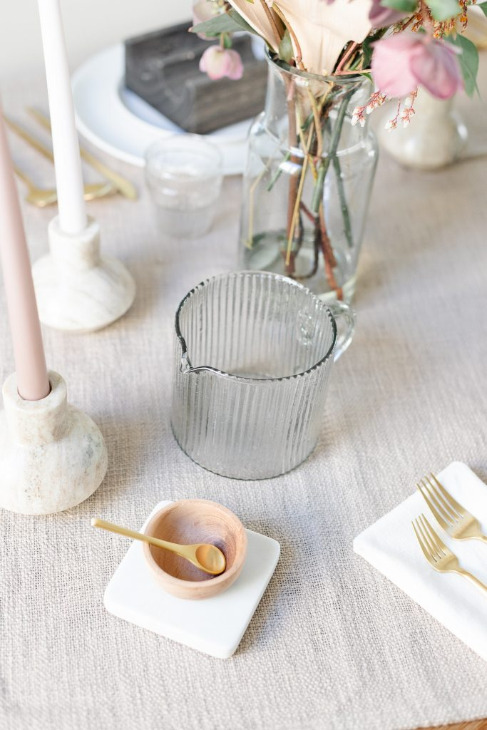small wooden bowl with brass spoon and ribbed clear glass carafe