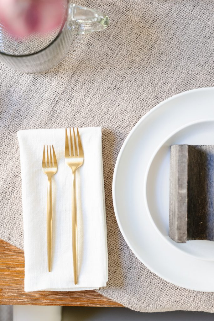 gold flatware next to white dinner plate on dining room table
