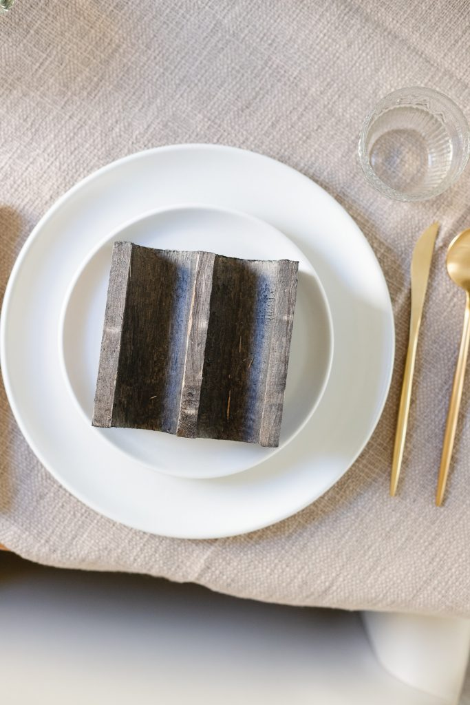 taco holder on white dinner plate with gold flatware