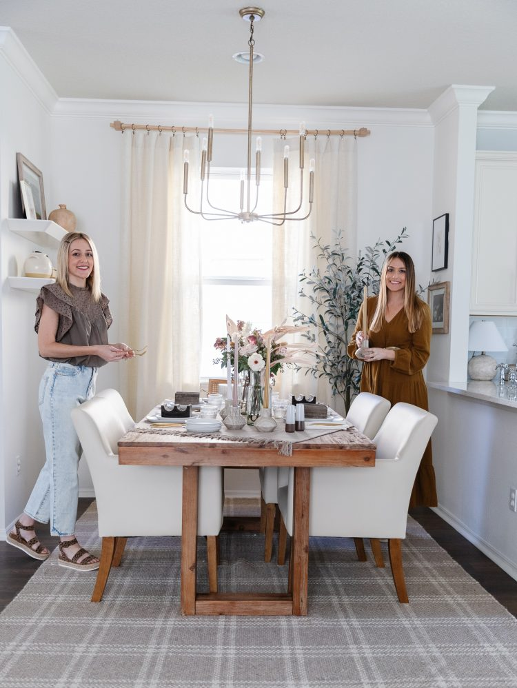 two women setting a tablescape in dining room