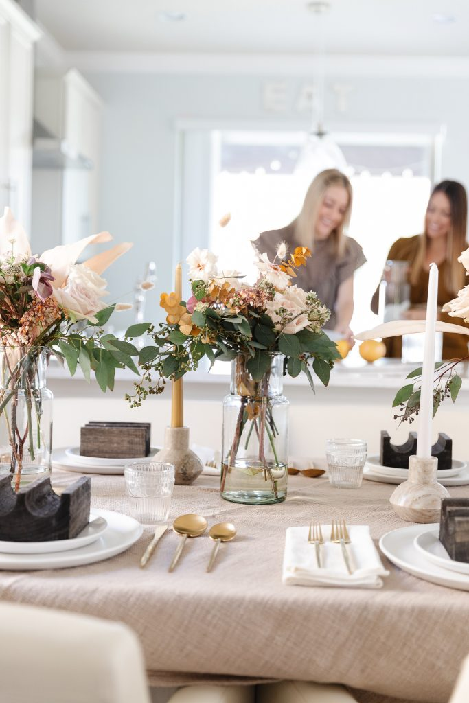 tablescape set with florals with two women in background