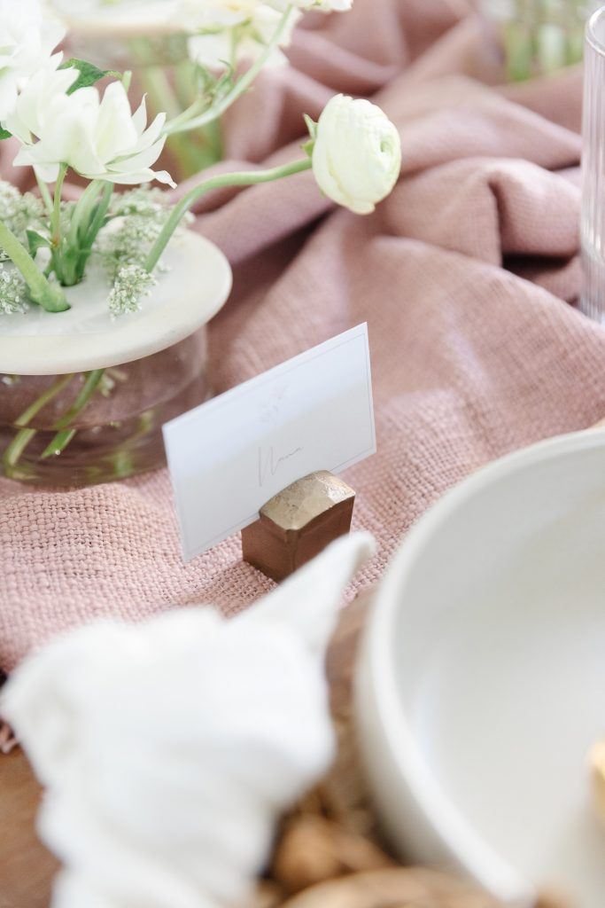 chiseled brass place card holder on dining room table for designer-level styling
