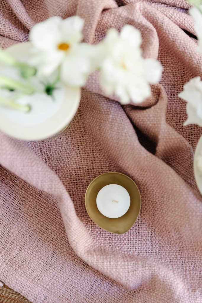 throw blanket with tea light and white flowers