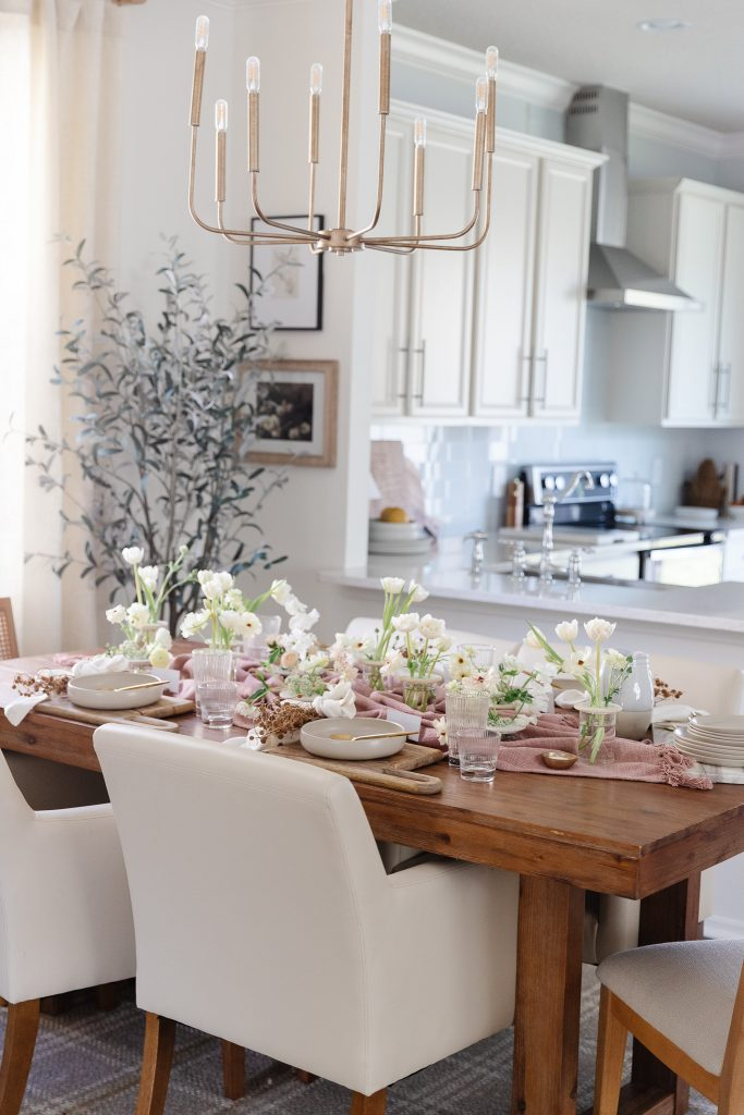 natural wood dining room table with kitchen in background
