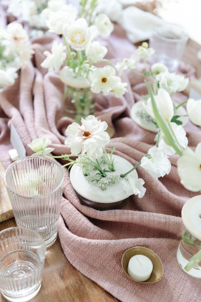 white flowers and throw blanket on dining room table with tealight