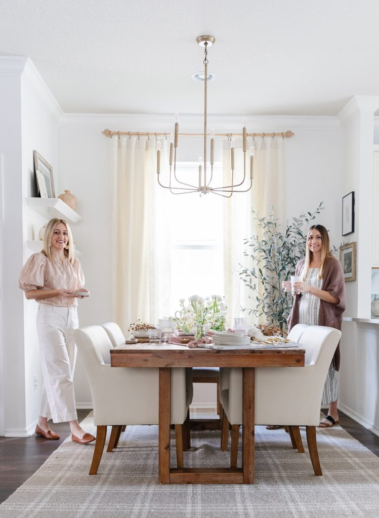 two women setting a dining room table