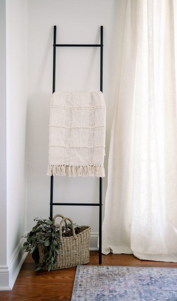 cream colored throw blanket on black ladder against wall