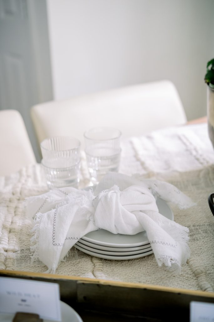 white plates stacked with white dinner napkins folded on top