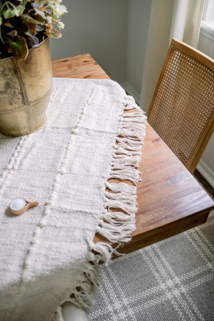 cream colored throw blanket on natural wood dining room table
