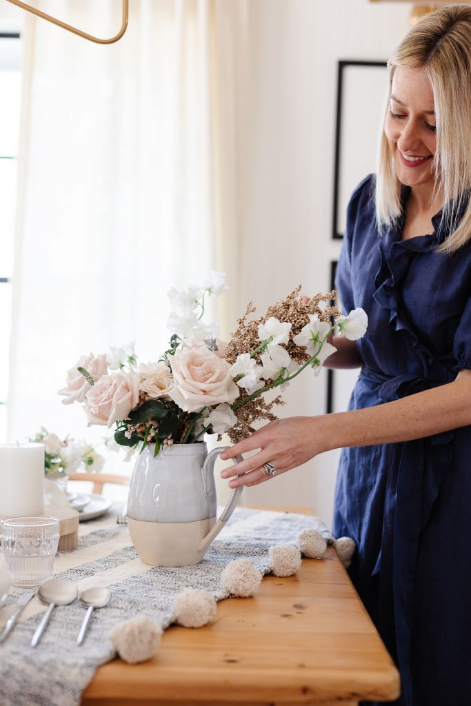 woman placing pitcher with floral arrangement on dining table
