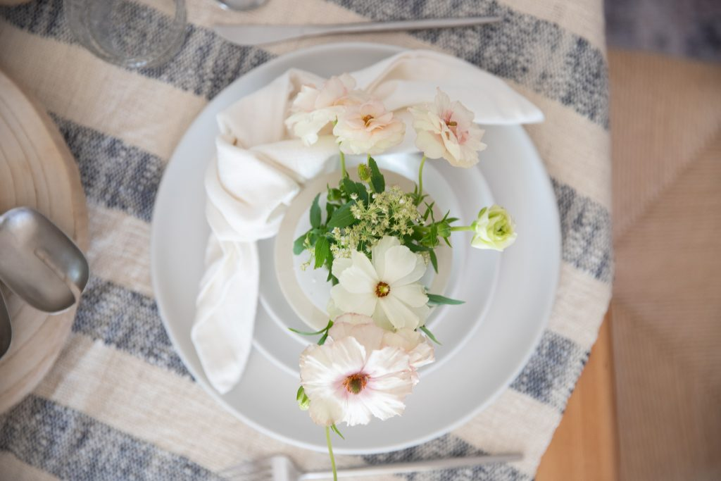white dinner plates with napkin and floral centerpiece