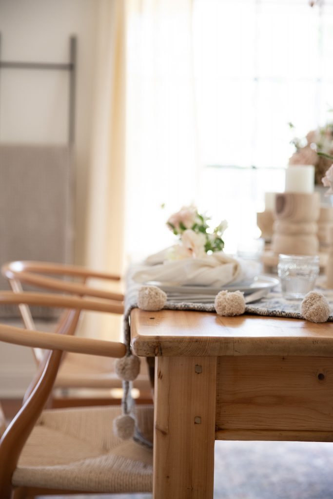 natural wood dining room table with place settings