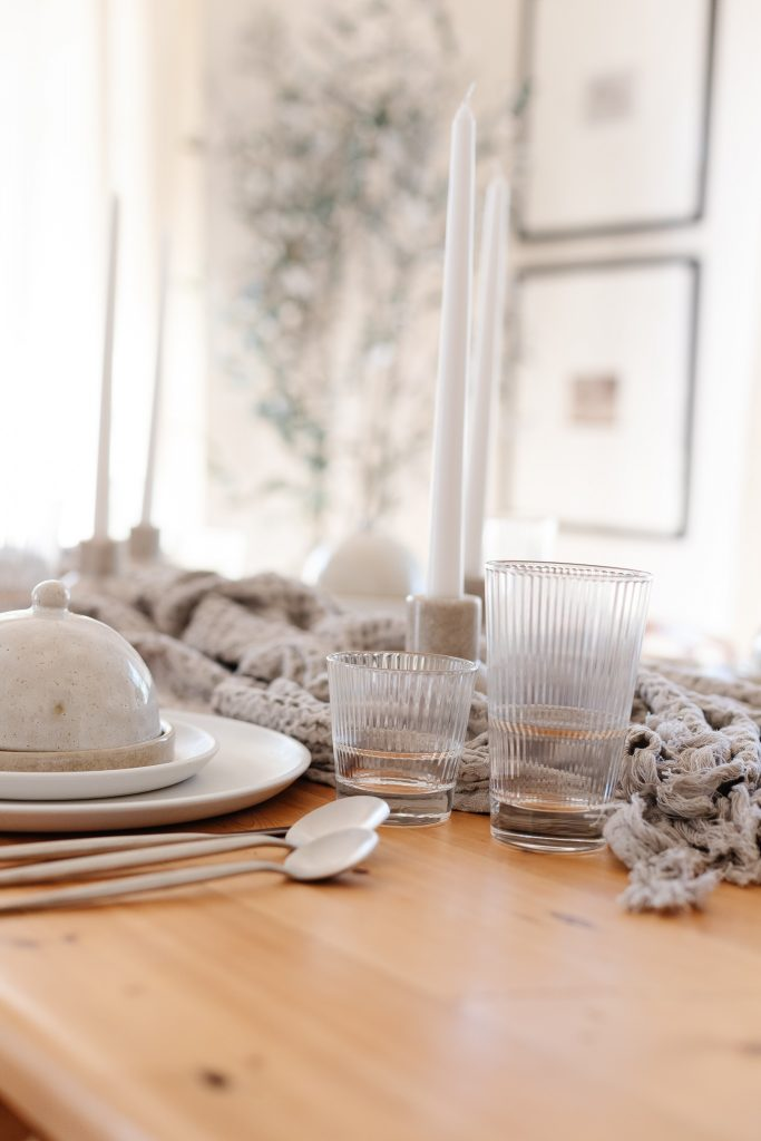 dinnerware, flatware and glassware on dining room table with taper candles