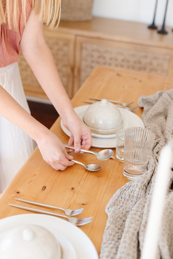 woman setting table with brushed silver flatware