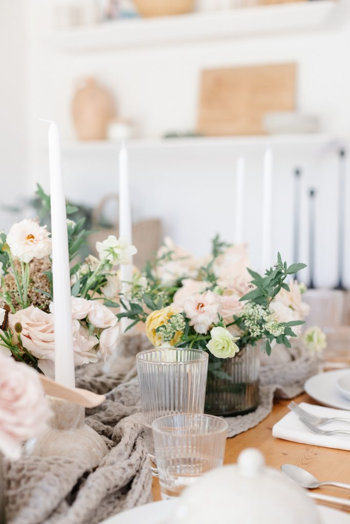 tablescape on dining room table with white taper candles and blush florals; timing etiquette; show up late